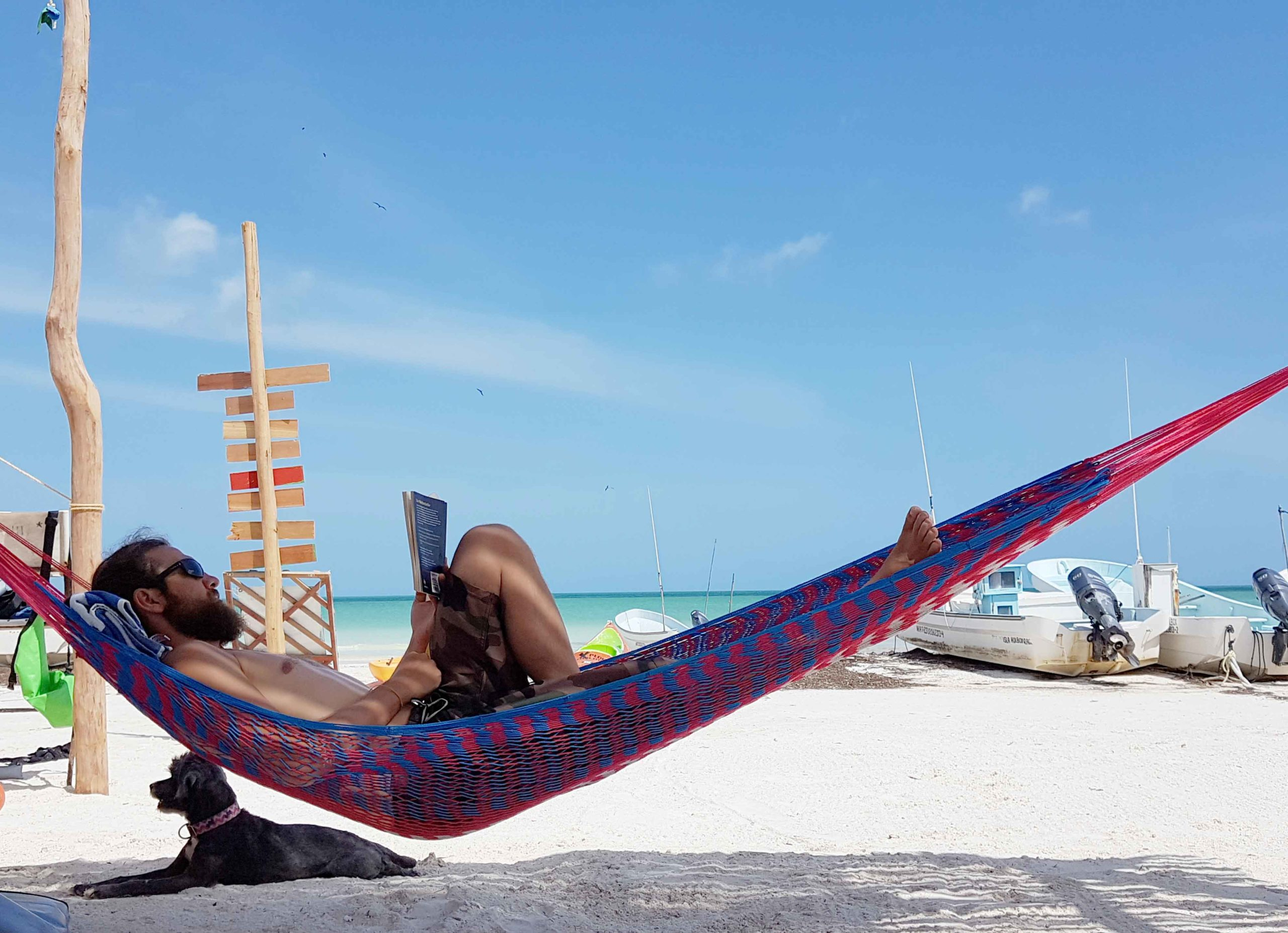 Alex in der Hängematte am weißen Sandstrand auf der Isla Holbox in Mexiko