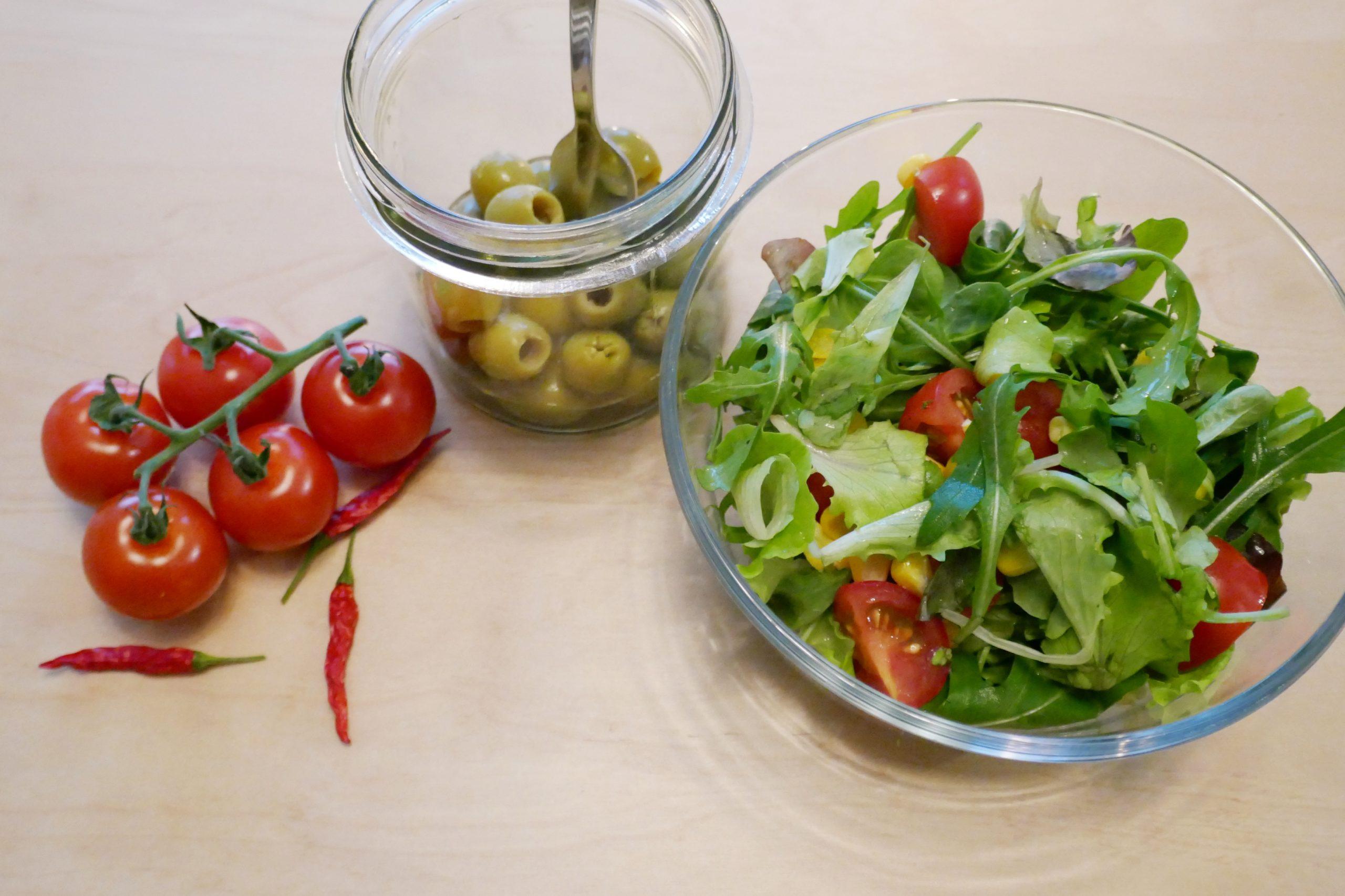 Cocktailtomaten, grüne Oliven, Salat und Chilis