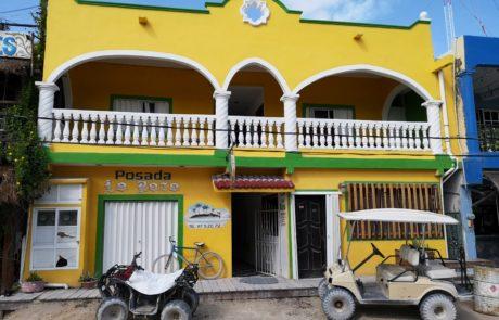 Gelbes Haus mit Golfcart und Quad auf der Isla Holbox in Mexiko