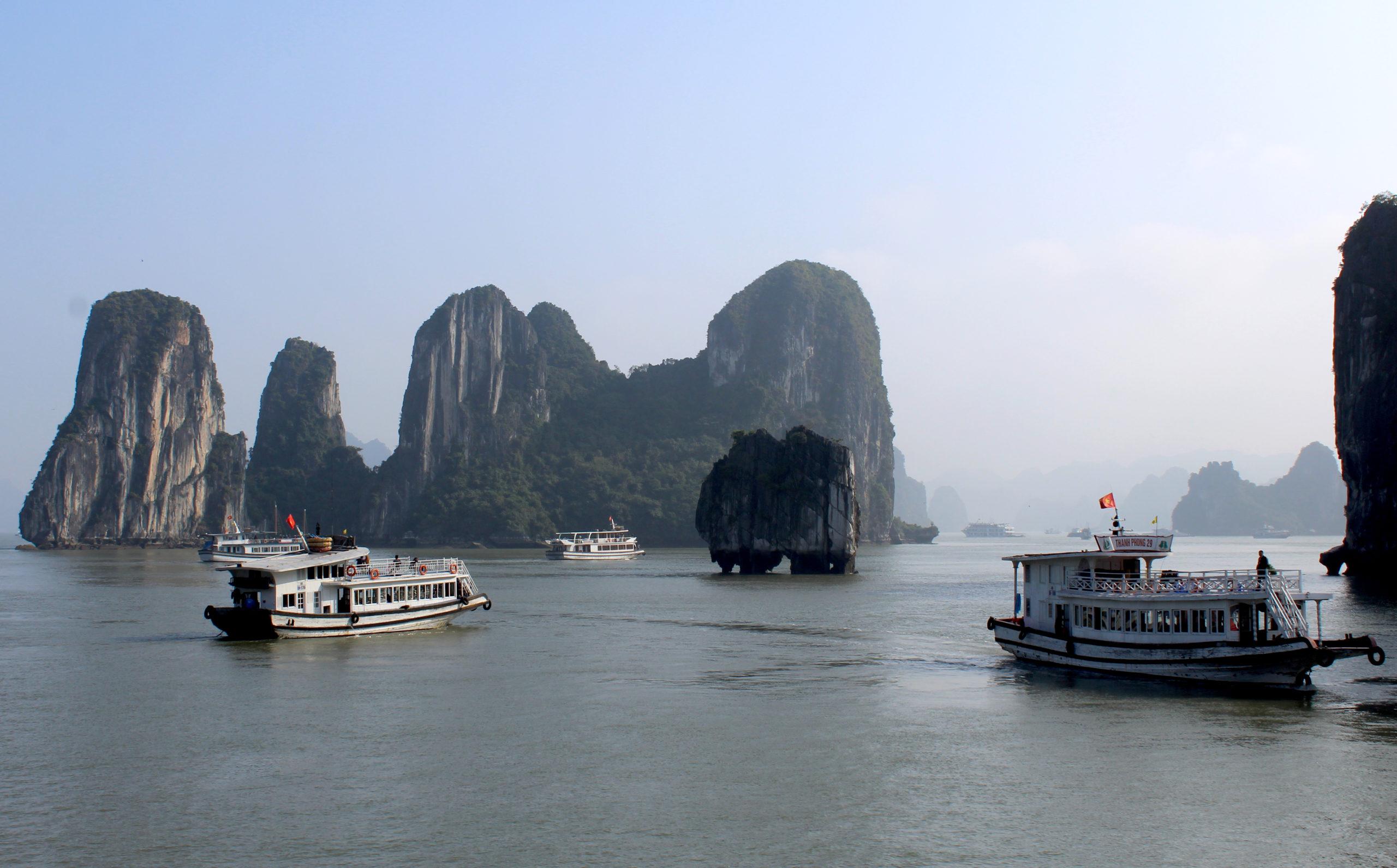 Schiffe vor einer Kalksteininsel in der Ha-Long-Bay in Vietnam