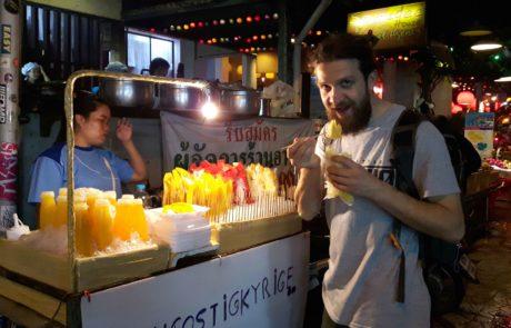 Mann isst frisch aufgeschnittene Mango am Street Food Stand am Nachtmarkt von Chiang Mai, Thailand