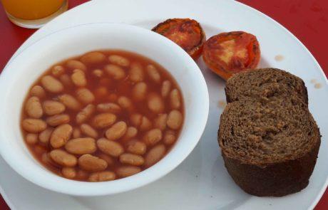 Veganes Frühstück, Baked Beans, Brot und gegrillte Tomaten in Bangkok, Thailand