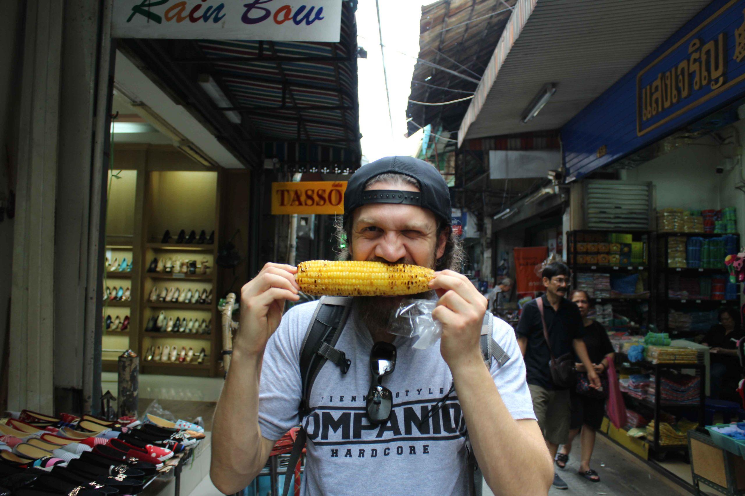 Mann isst gegrillten Maiskolben in Chinatown in Bangkok, Thailand
