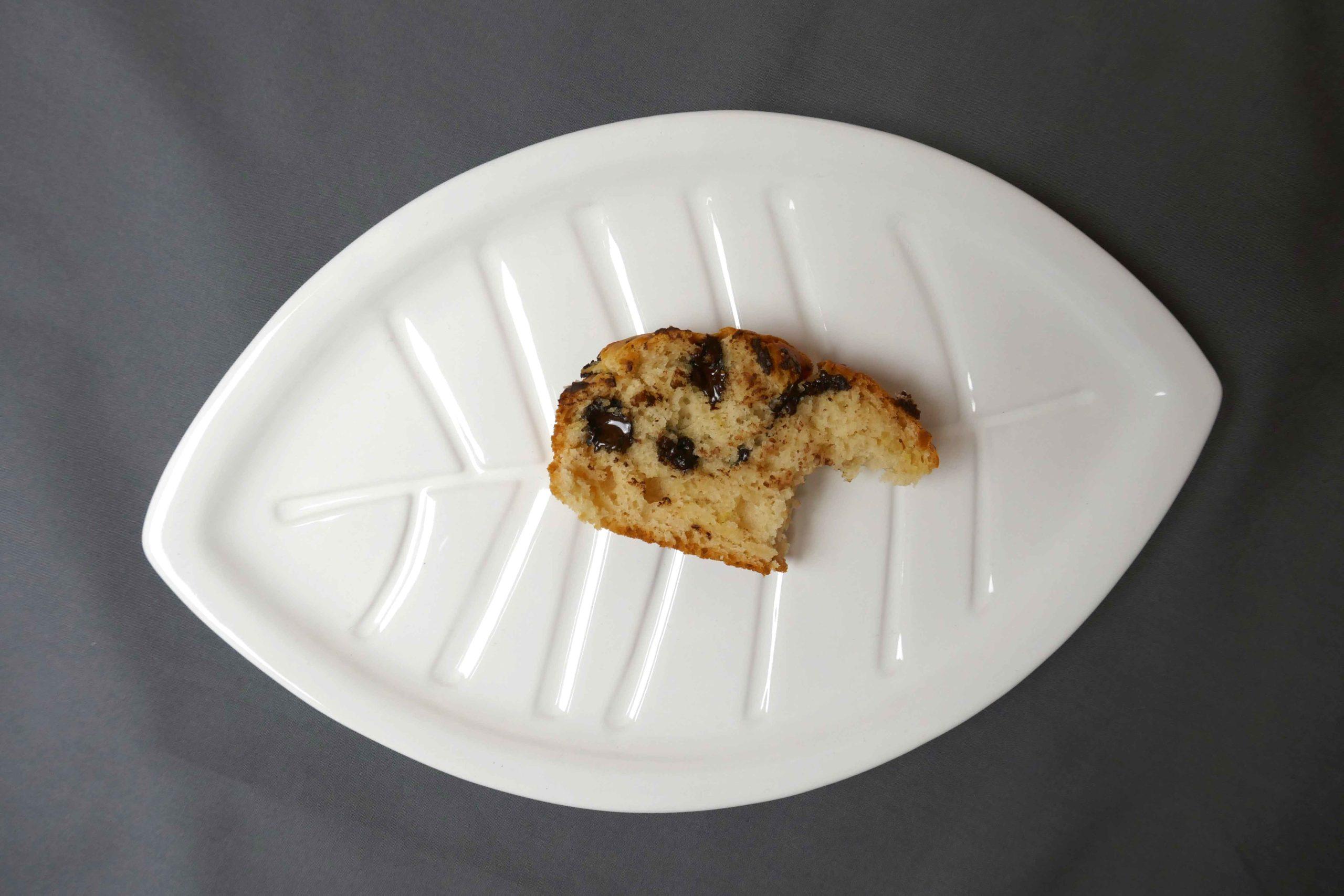 Scheibe Zitronenkuchen mit Schokostückchen auf einem Teller mit Blattform