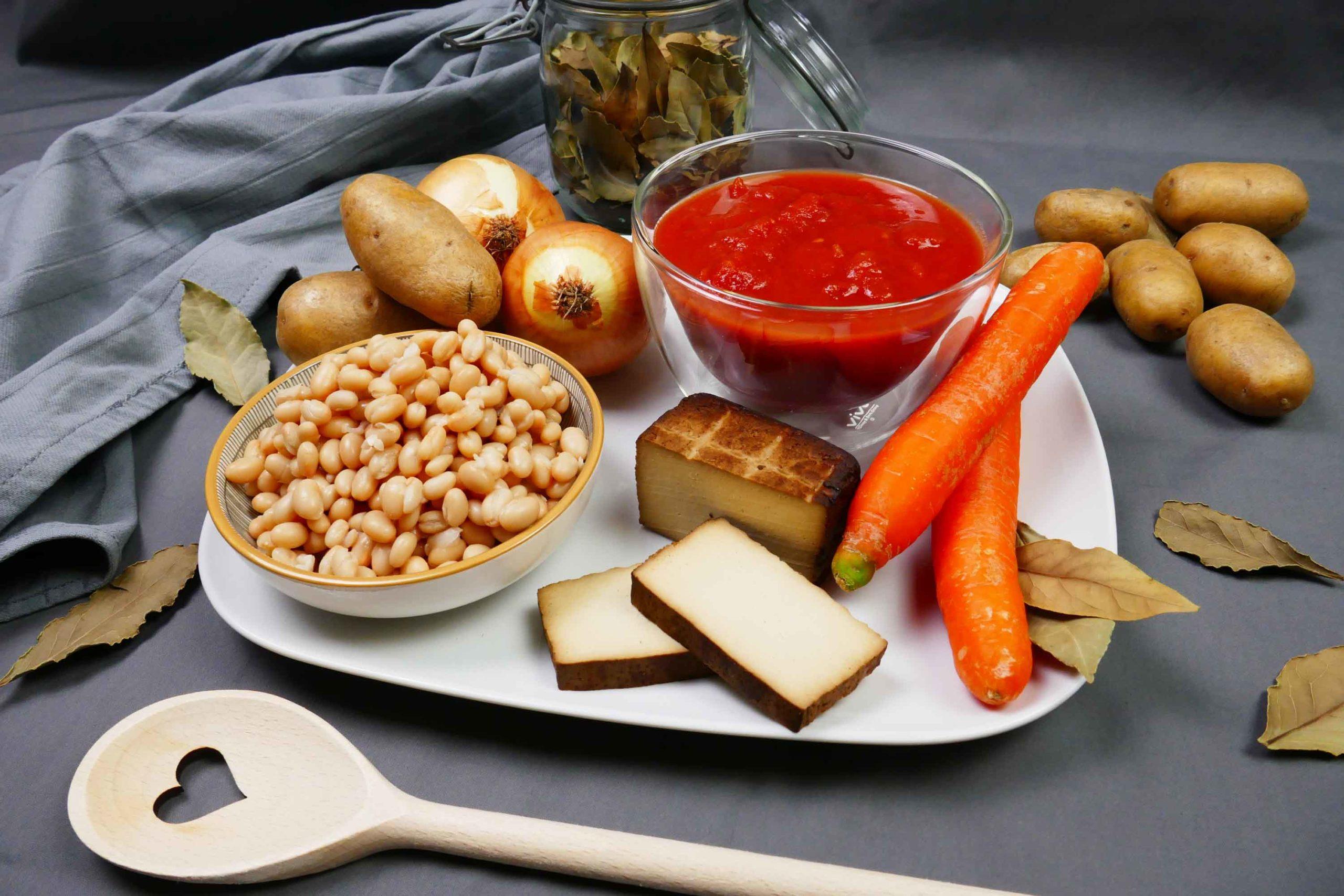 Serbische Bohnensuppe Zutaten, weiße Bohnen, geräucherter Tofu, Karotten, Tomatenpassata, Kartoffeln, Lorbeerblätter, Kochlöffel