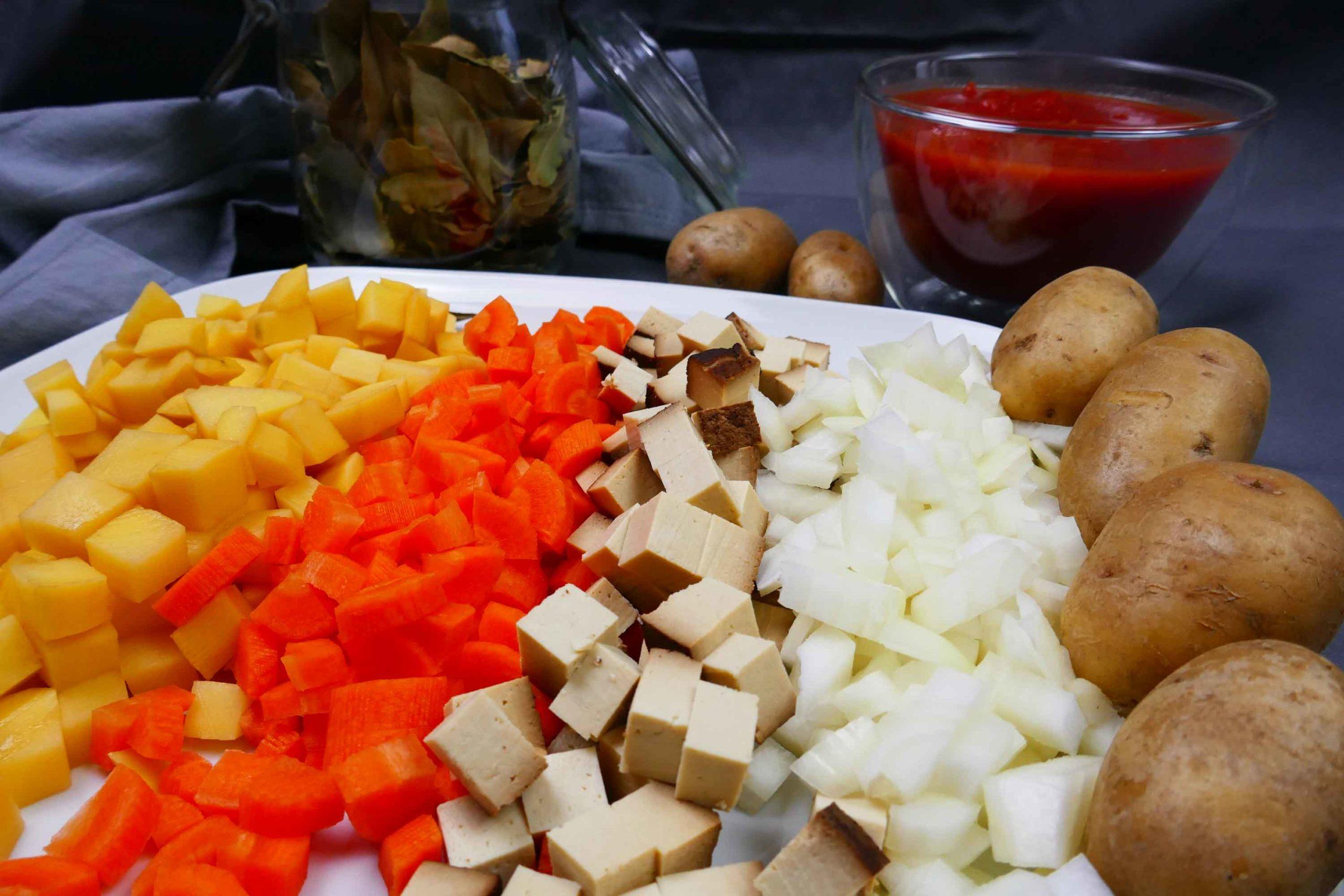 Zutaten für die vegane Serbische Bohnensuppe gewürfelt, Zwiebeln, geräucherter Tofu, Karotten, Kartoffeln, Tomatenpassata