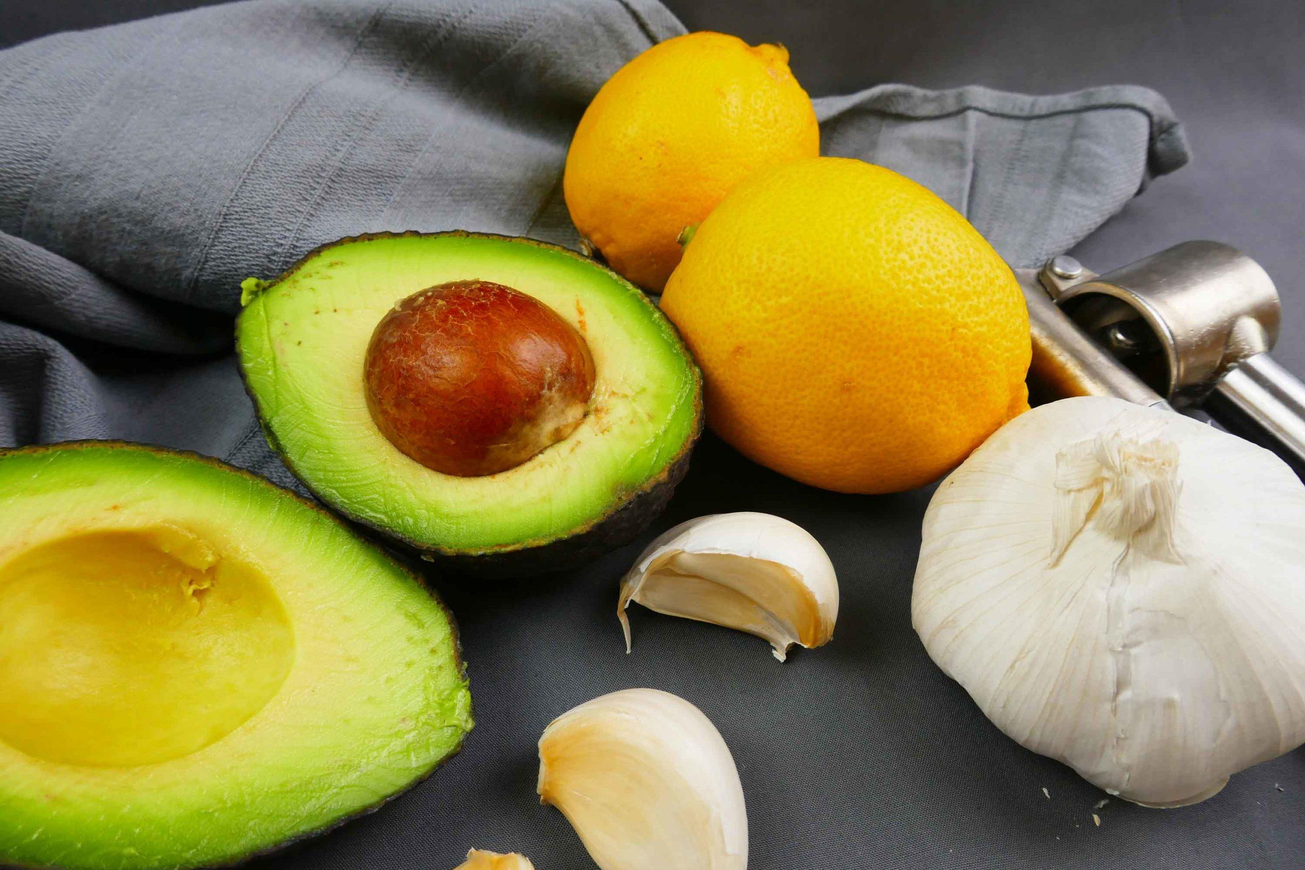 Zutaten für das Avocadotopping, frische Avocado, Knoblauch und Zitrone, Knoblauchpresse
