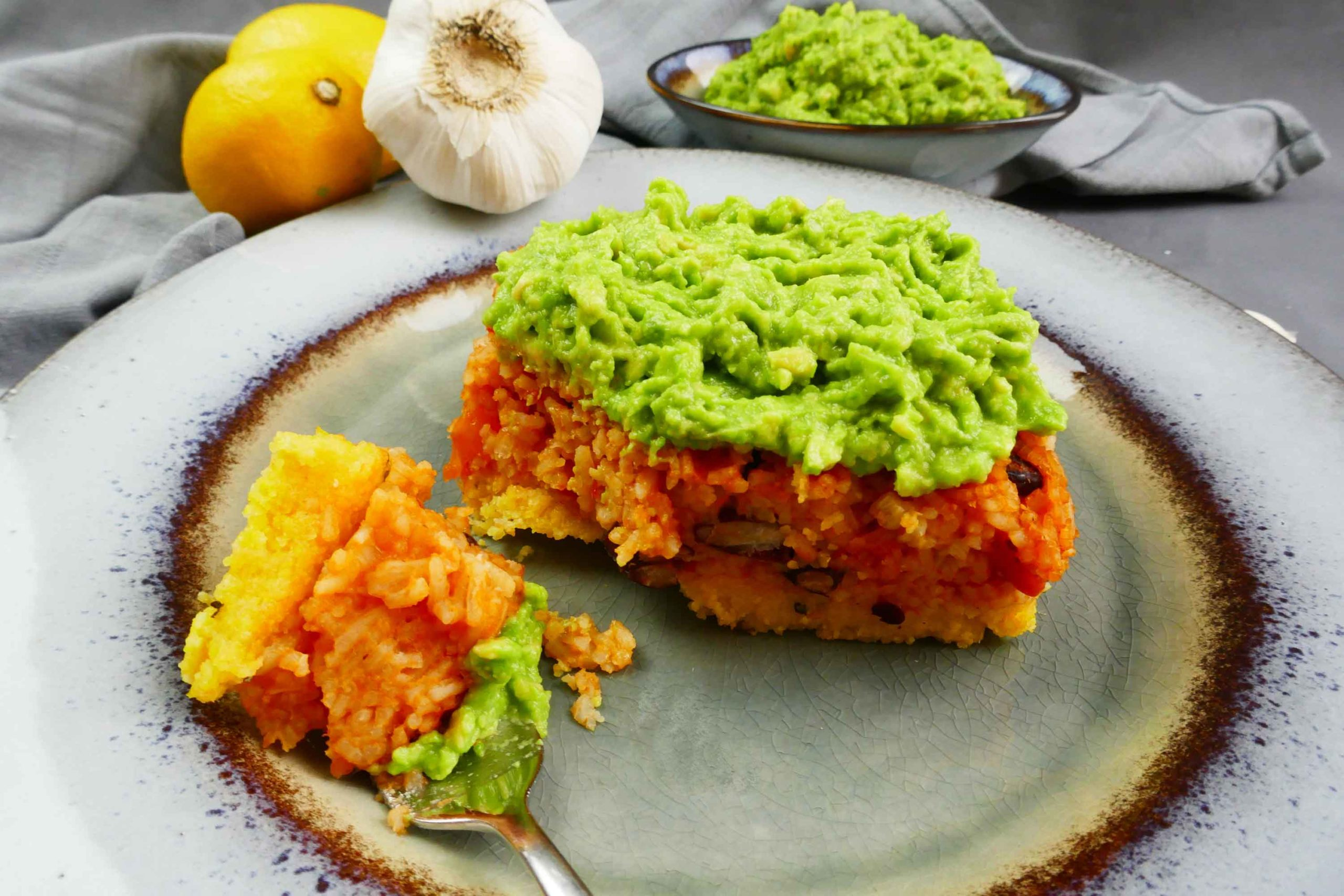 Polentaschnitte mit Reis und Bohnen und frischer Avocado als Topping auf einem Teller angerichtet