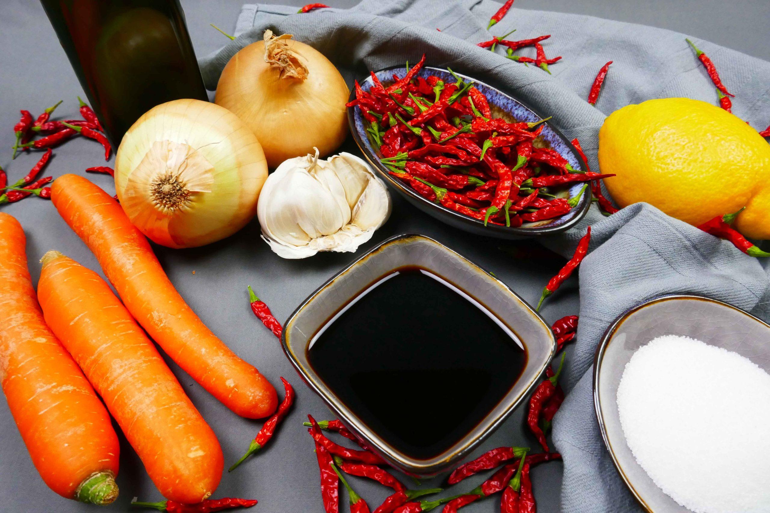 Zutaten für die vegane Tom Yam Chili Paste, dunkle und helle Sojasauce, Zucker, Zitronen, Chilischoten, Thaichilis, Zwiebeln, Knoblauch und Karotten